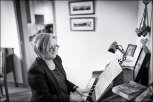 black and white photographic portrait of woman playing the piano