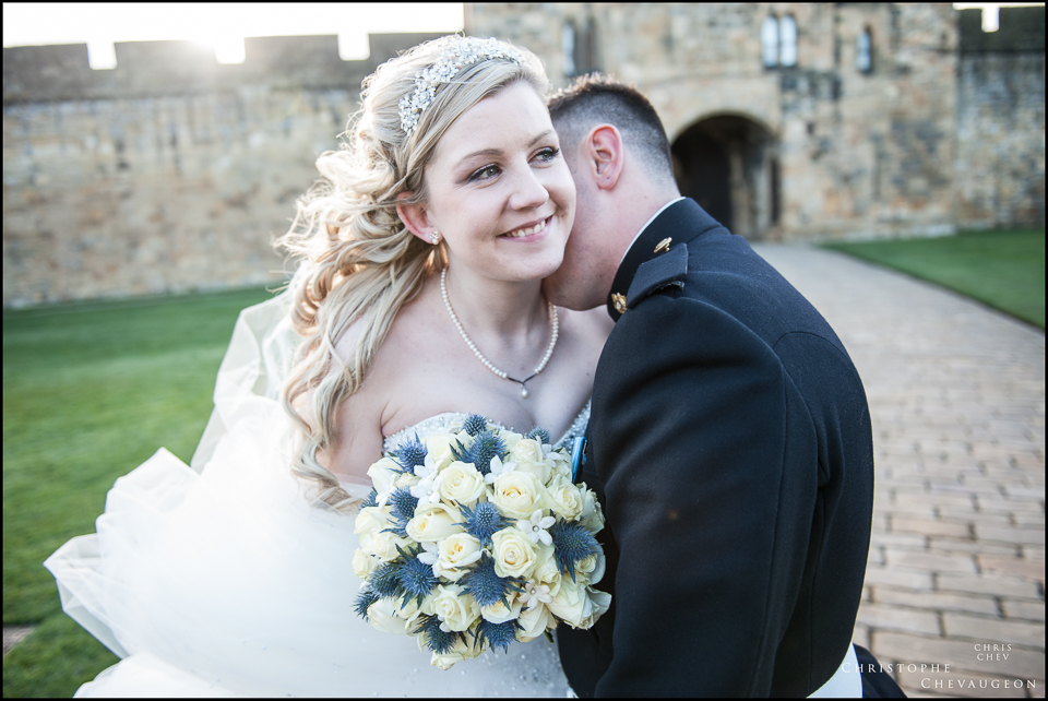 bride and groom embrace at Alnwick Castle