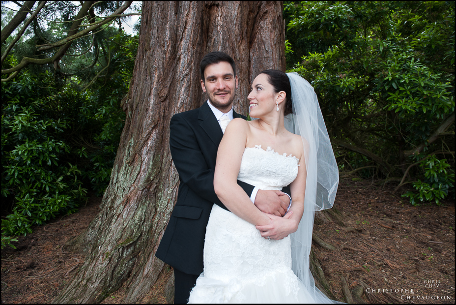 Bride and Groom embracing against a tree at Linden Hall Northumberland