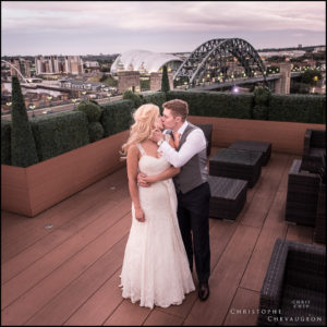 Bride and Groom on the Vermont hotel Sky Lounge for a kiss as the light fails. Photography by ChrisChevPhotographer